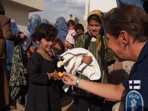 Naissotilas tervehtimässä afganistanilaisia lapsia ja naisia.