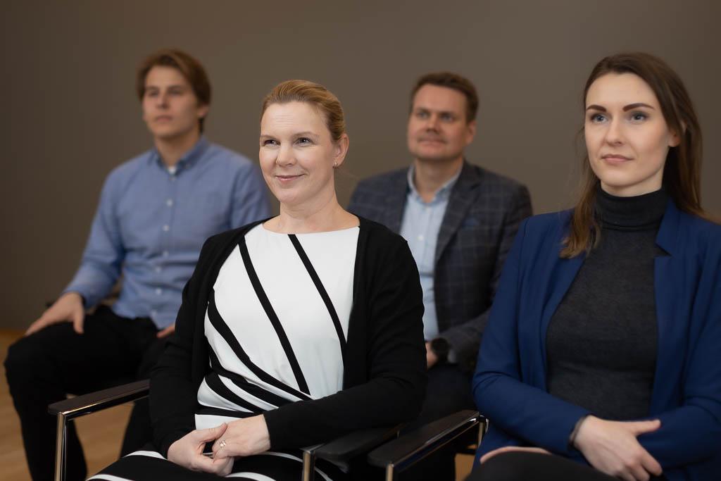 Eturivissä kaksi naista istuu ja katsoo eteenpäin, takarivissä vastaavasti kaksi miestä.