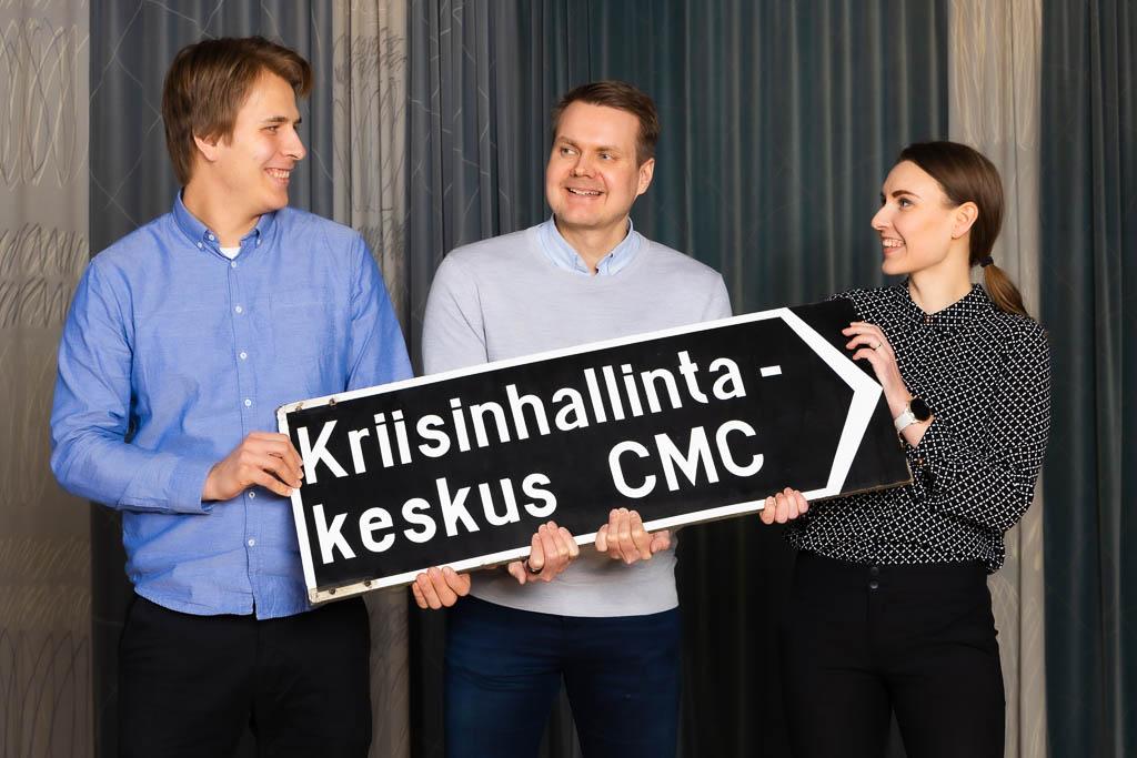 Kaksi miestä ja yksi nainen seisoo ja kannattelee hymyillen edessään kylttiä, jossa lukee Kriisinhallintakeskus CMC. Taustalla siniharmaa verho.