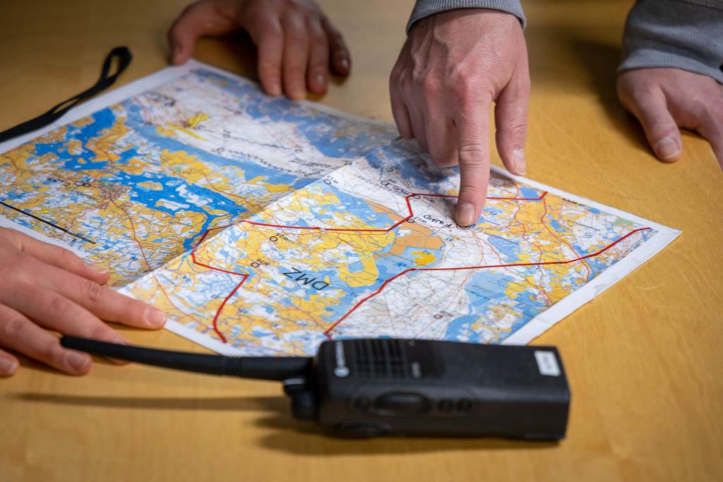 Pöydällä avoinna kartta, kahden henkilön kädet, toinen osoittaa sormella karttaa, etualalla radiopuhelin.