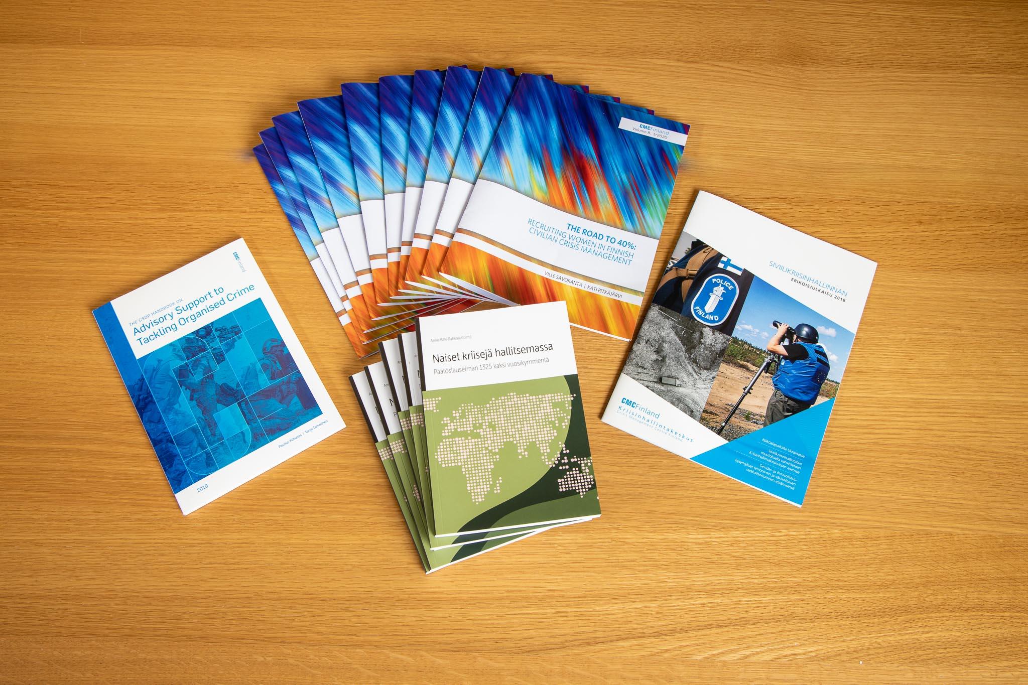 Neljä erilaista julkaisua aseteltuna viuhkamaisesti pöydälle.