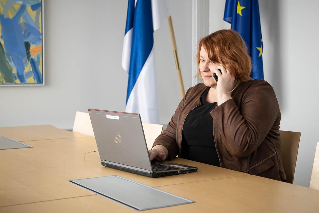 Nainen istuu pöydän ääressä, puhuu puhelimeen ja käyttää samalla kannettavaa tietokonetta. Taustalla kokoushuoneessa Suomen ja EU:n liput sekä värikään taulun kulma.