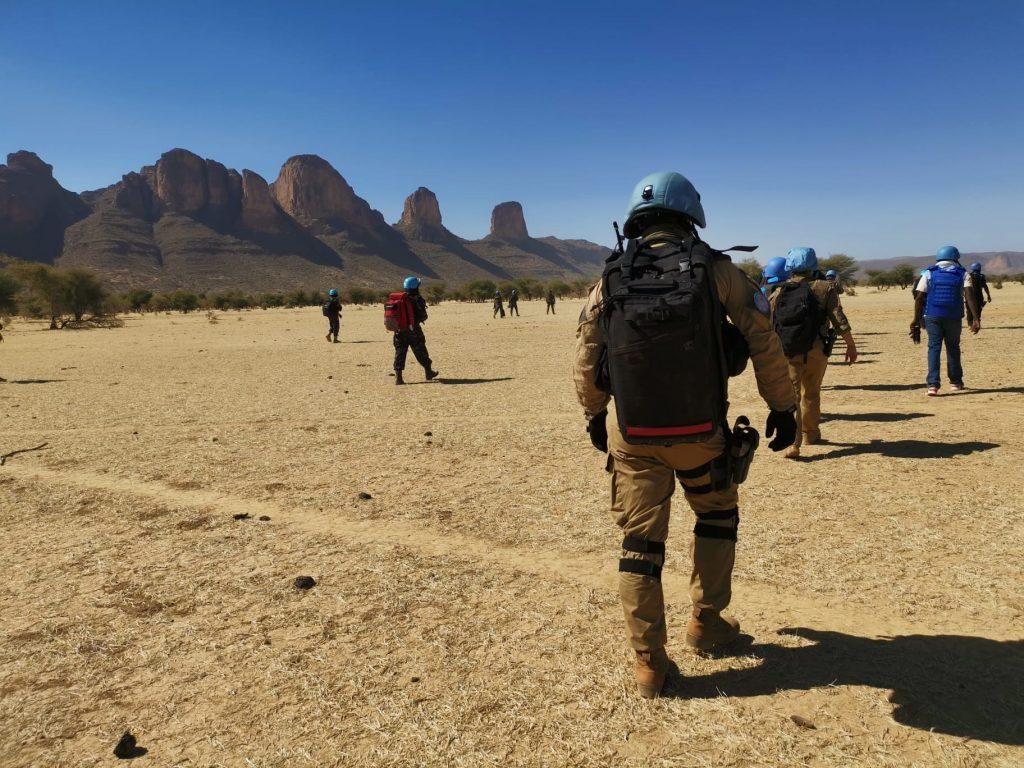 Henkilöitä kävelemässä selin kameraan, aukea maisema Malissa, taustalla vuoria.