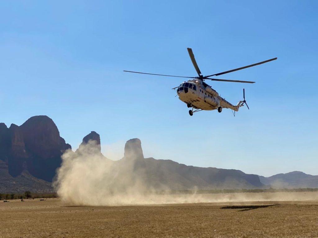 Helikopteri laskeutuu Malissa aukealle, paljon pölyä.