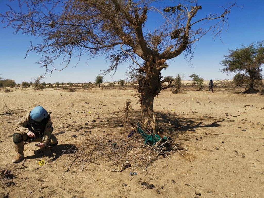 Henkilö kumartuneena tutkimaan maassa olevia jälkiä Malissa.
