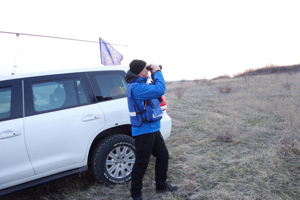 Mies sinisessä takissa ja mustissa housuissa seisoo valkoisen auton edessä ja kiikaroi kaukaisuuteen