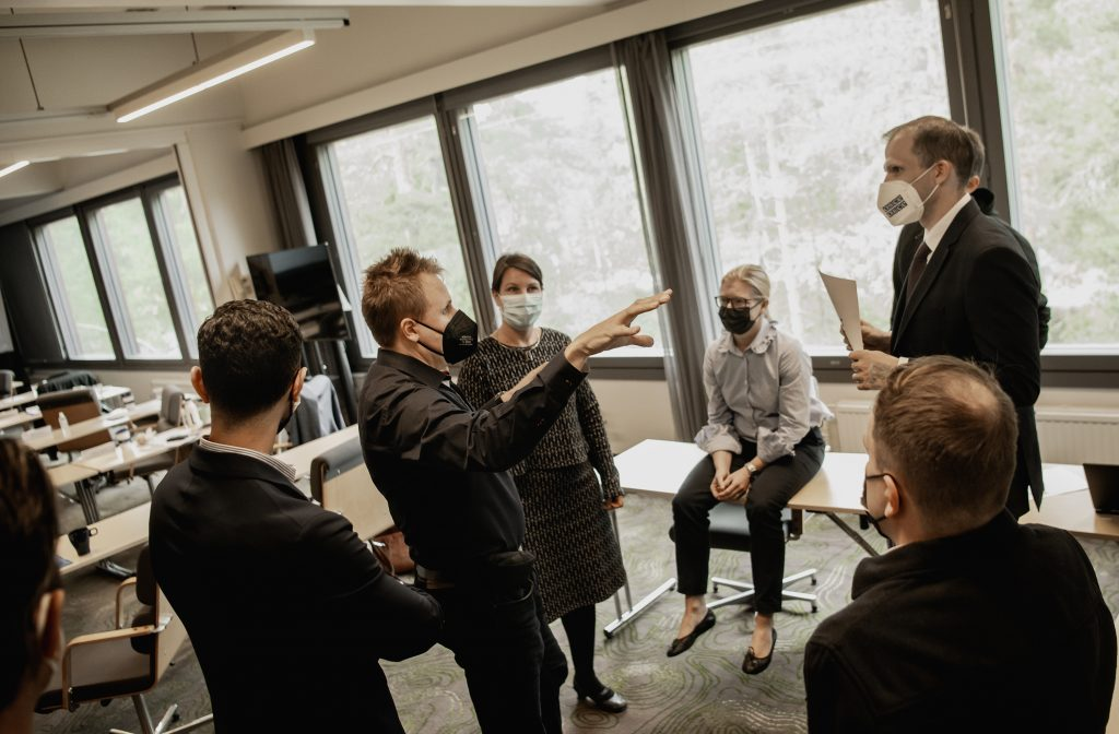 People standing in a cricle and discussing in a room during mediation course